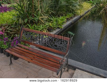 Classic wooden chair in the garden near the pond .