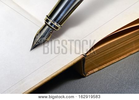 Open blank page of a book and the nib of a fountain pen