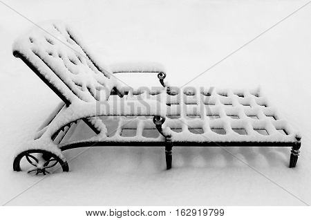 A metal lounge chair covered in snow concept or metaphor for a harsh winter season.