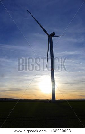 It is evening. The wind turbine looks very pretty by the sundown.