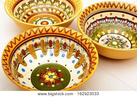 Traditional colored pottery. Painted ceramic plate. Painted ceramic multicolored plate.