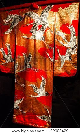 Kimono - Japanese national costume. Red embroidered textile.