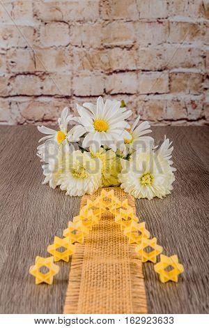 Jewish Holiday symbol pasta for broth buckwheat a pasta on a background of white flowers