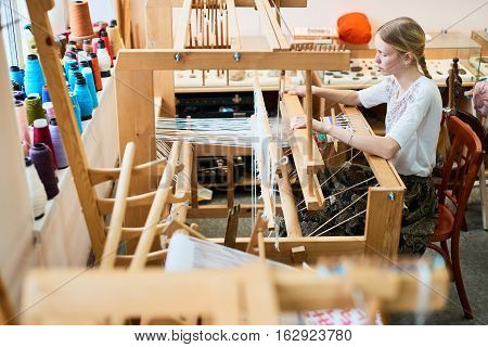 The girl in the production process of textiles are handmade on a loom