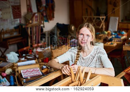 Portrait of a girl in the workshop of the weaver standing by loom with special tools in the hands of