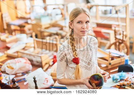 Portrait of a girl weaver in the workshop, standing with yarn in hand
