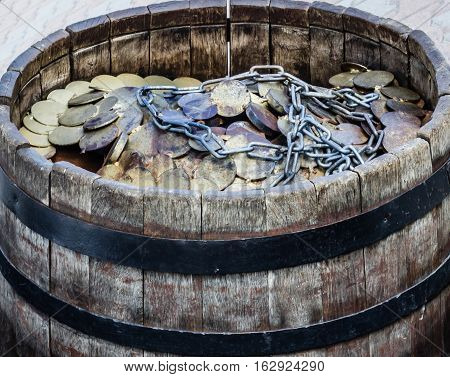 A lot of coins and chain in a wooden barrel