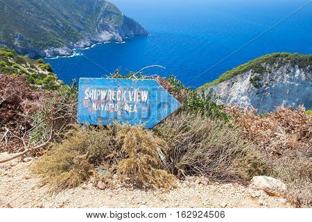 Zakynthos Greece - August 20 2016: Old blue wooden sign shows direction to Ship Wreck viewpoint Navagio bay Greece. The most popular natural landmark of Zakynthos Greek island in the Ionian Sea