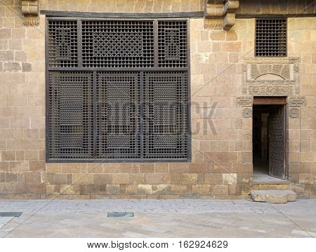Facade (Mashrabiya window and open wooden door on stone wall) of Beit (house) El Harrawi an old Mamluk era historic house in Medieval Cairo Egypt built in the eighteenths century