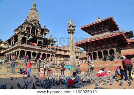 PATAN, NEPAL - DECEMBER 19, 2014: Durbar Square with Bishwanath Mandir temple, Garuda statue on column and Krishna Mandir temple