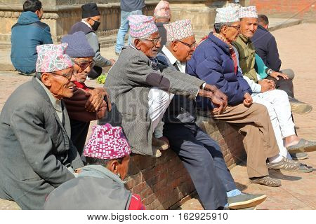 PATAN, NEPAL - DECEMBER 20, 2014: Nepalese men gathering and wearing Dhaka Topi (traditional Nepalese hat) at Durbar Square