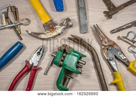 Old tools on wooden background. The metal parts of the tool covered with rust. Composition 3.