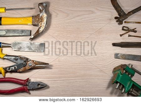 Old tools on wooden background. The metal parts of the tool covered with rust. Composition 5.