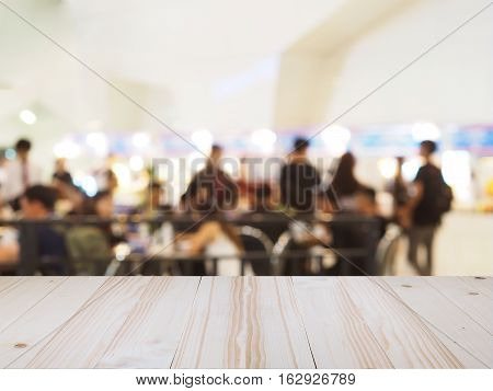 Perspective wood and blurred food court with crowd people. product display template.