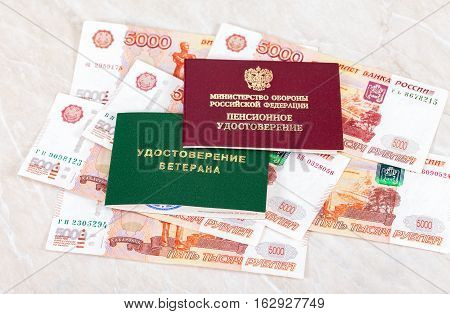 MOSCOW RUSSIA - DECEMBER 18 2016: Russian Pension Certificate and Veteran Certificate lying over banknotes. Inscription on Certificate in russian: