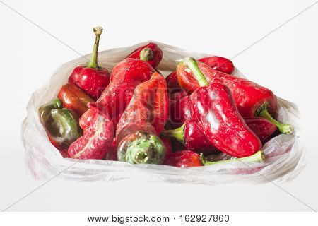 Freshly harvested red peppers dirty ground in a white envelope to understand a concept of agriculture and healthy eating