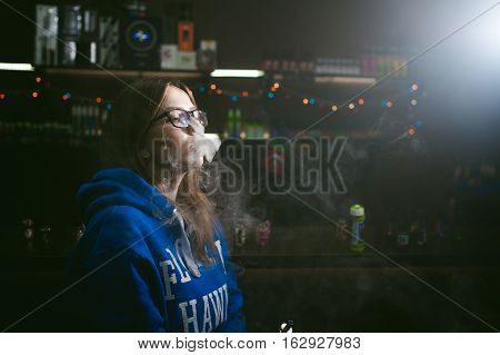 Beautiful Young Woman With Glasses Smoking Electronic Cigarette. Girl In A Blue Sweater Blows Clouds