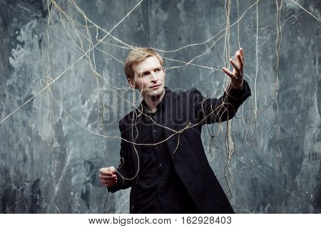 Young man tries to break the shackles. Concept of manipulation and slavery