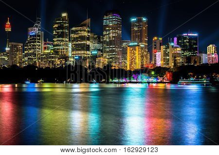 Sydney, Australia - May 29, 2016: Long exposure of city skyline by night from Mrs Macquarie's Chair, featuring light show. High resolution vibrant image with some light streaks caused by passing boats.