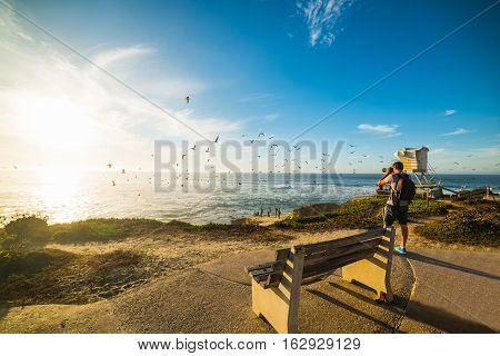 Photographer taking a picture in La Jolla at sunset California