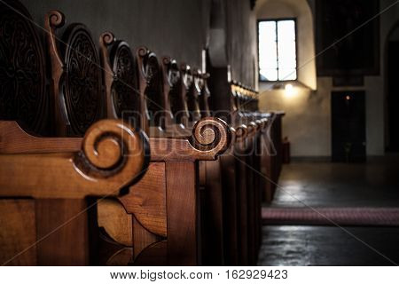 Row of wooden benches inside a church in Spain.