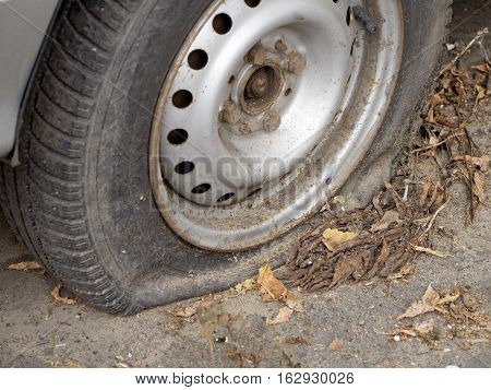 Flat tire of a passenger car on a road