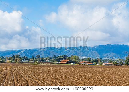 Farmhouse in a ploughed field in California USA