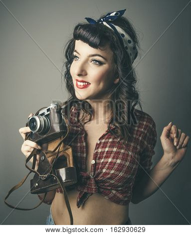Half body portrait of smiling trendy young woman in check 60s style top with retro camera