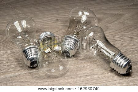 Electric light bulbs on wood background. Bulbs are four of them. They do not shine.