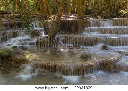 Deep forest multiple layer blue stream waterfall, natural landscape background