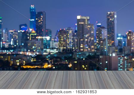 Opening wooden floor, Night blurred lights central business downtown, abstract background
