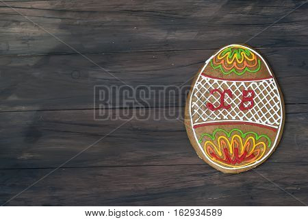 Homemade painted Gingerbread cookies in the shape of the Easter egg on a dark wooden table.Top view. Copy space. family holiday present preparations food photo