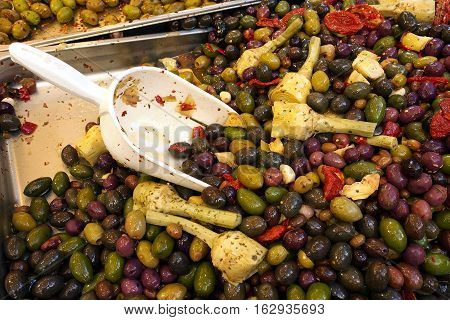 Street food market. Different kind of olives and artichokes with spices and chili pepper.