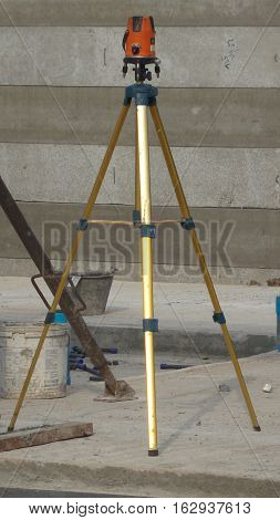 Close-up to automatic level tripod in construction site