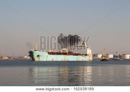 Chemical Vessel leaving the port of Ventspils, tug boat supporting.