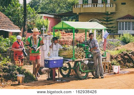 Goa, India - November 16, 2012: Young Indian men cooking and selling India's popular street reed juice in a busy touristy place - the entrance to the Dudhsagar Waterfall