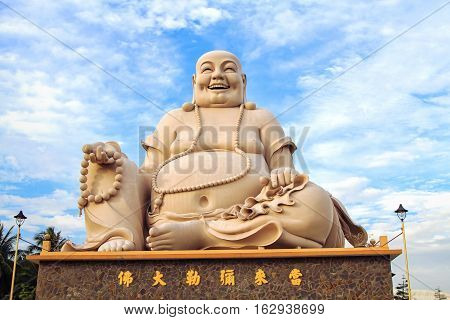 Massive statue of the Sitting Smiling Buddha at the Vinh Tranh Pagoda in My Tho the Mekong Delta Vietnam