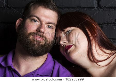 Young couple photographed close to one another in a romantic pose.