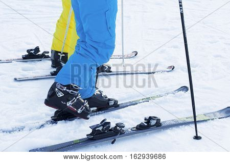 Feet put in ski boots and skis and blue-yellow trousers