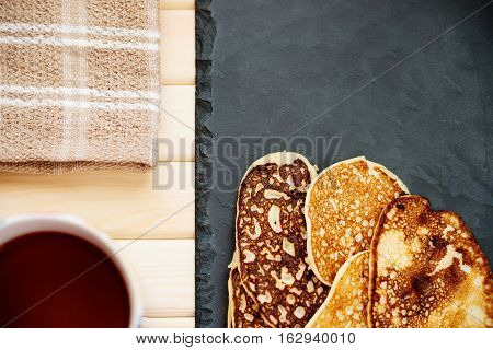 Cup of tea, tablecloth and fritters on a table