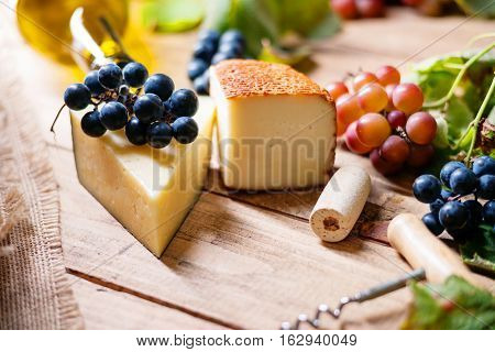Cheese, grape and wine cork on a wooden table