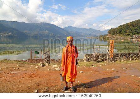 POKHARA, NEPAL - JANUARY 4, 2015: A Sadhu (Holy man) posing along the shore of Phewa Lake