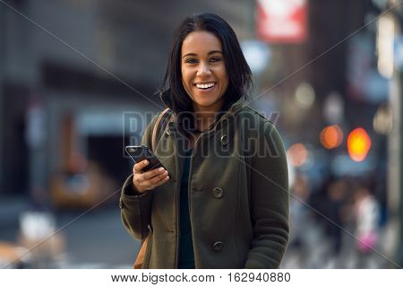 Beautiful young happy latin woman texting on mobile phone on city street. Student girl walking and texting on cell phone outdoors on city street at winter time.
