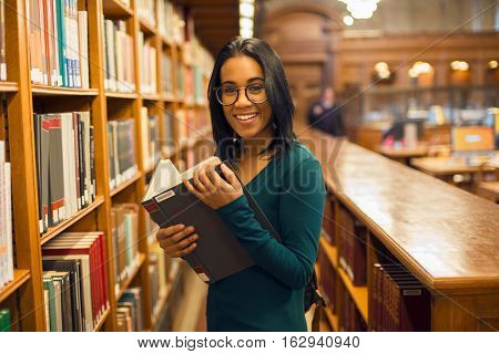 Happy smiling african american student girl reading book at library wearing eyeglasses. Woman studying in the library. People learning getting college degree concept.