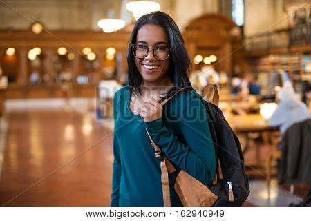 Happy college student girl with backpack in the library smiling. Beautiful young student woman in reading room. Education smile study learning