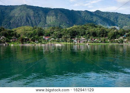 View to Samosir Island from Tuk-Tuk peninsula with nice reflections in the Lake Toba, North SUmatra, Indonesia