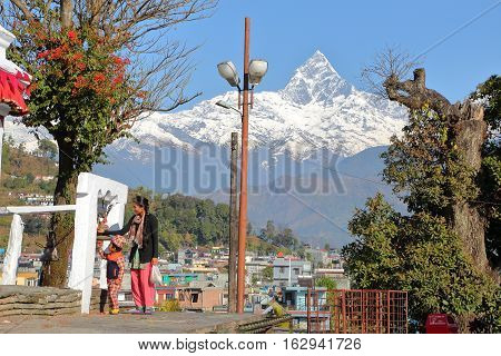 POKHARA, NEPAL - JANUARY 9, 2015: A Nepalese woman with her son ringing a bell at Bindhya Basini Temple (Himalaya mountains with Machapuchare Peak in the background)