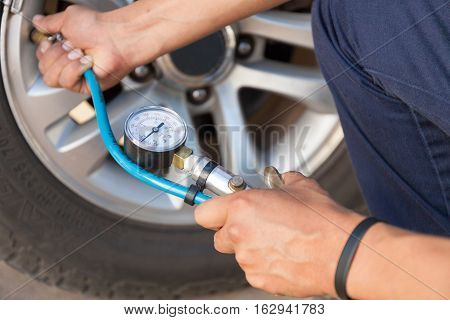 Hand holding gauge for car tyre pressure measurement. stock photo