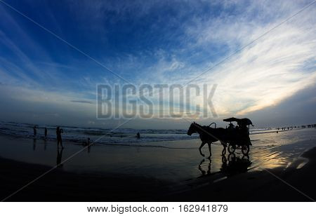 Silhouettes of horse with a cart and people relaxing at Parangtritis Beach famous by its black sands, Central Java, Indonesia.