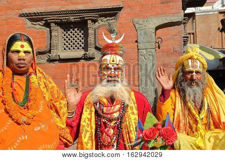 KATHMANDU, NEPAL - JANUARY 14, 2015: Portrait of Three Sadhus (Holy man), one woman and two men at Durbar Square